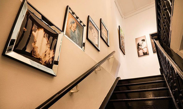 Wooden stairwell lined with portraits at White Room Studio Singapore