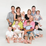 Family multi generation photoshoot of a large Caucasian family with grandparents, parents and grandchildren with white background