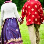 Bridal Photography Singapore bride and groom in traditional indian clothing holding hands and walking in grassy field outdoor photoshoot