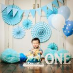 Cake Smash Photography Singapore baby boy toddler celebrating first birthday with special cake and blue party decorations