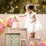 Cake Smash Photography Singapore toddler young girl standing on stool to touch birthday cake with large number 1
