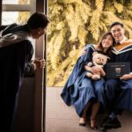 Convocation Photoshoot Package Singapore graduate couple sitting on ledge with teddy bear toy and graduate degree with father looking on by door frame