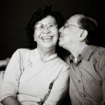Couple Photography Singapore elderly couple sitting down man kissing smiling woman's cheek black and white portrait photography