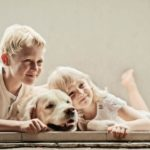 Pet Photography Singapore 2 young children smiling and leaning on white dog natural light photography