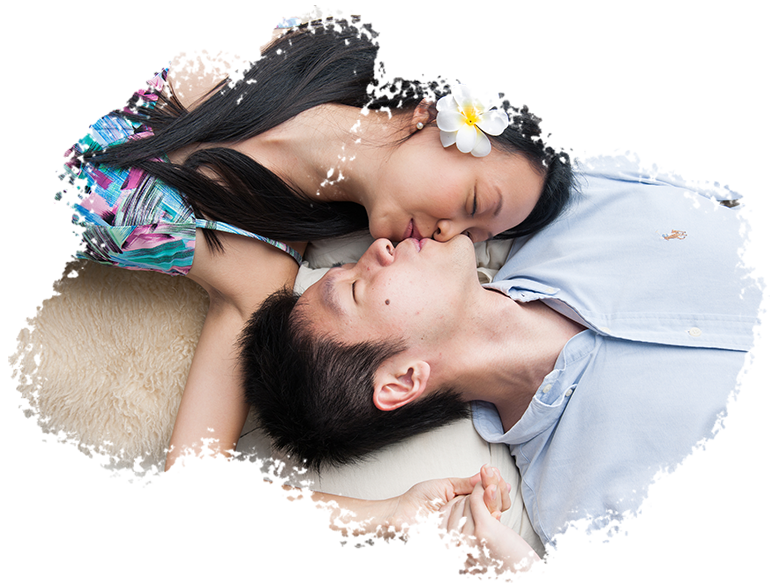 Couple Photoshoot Singapore man and woman kissing side by side while lying down on white pillows and fur rugs