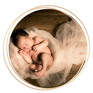 Newborn Baby Photography baby curled up resting on white mesh cloths