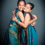 Family kids photography two girl children dressed in cultural Indian dressing blue saris hugging and smiling