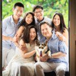 Family photoshoot studio photography of family of six huddled together with pet dog corgi