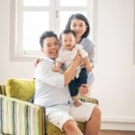 Professional family photoshoot Singapore father sitting on arm chair holding toddler child and mother standing posing for photos