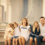 Outdoor family kids photography session of a smiling Caucasian family with 3 children and a pet dog with the Singapore Flyer in the background