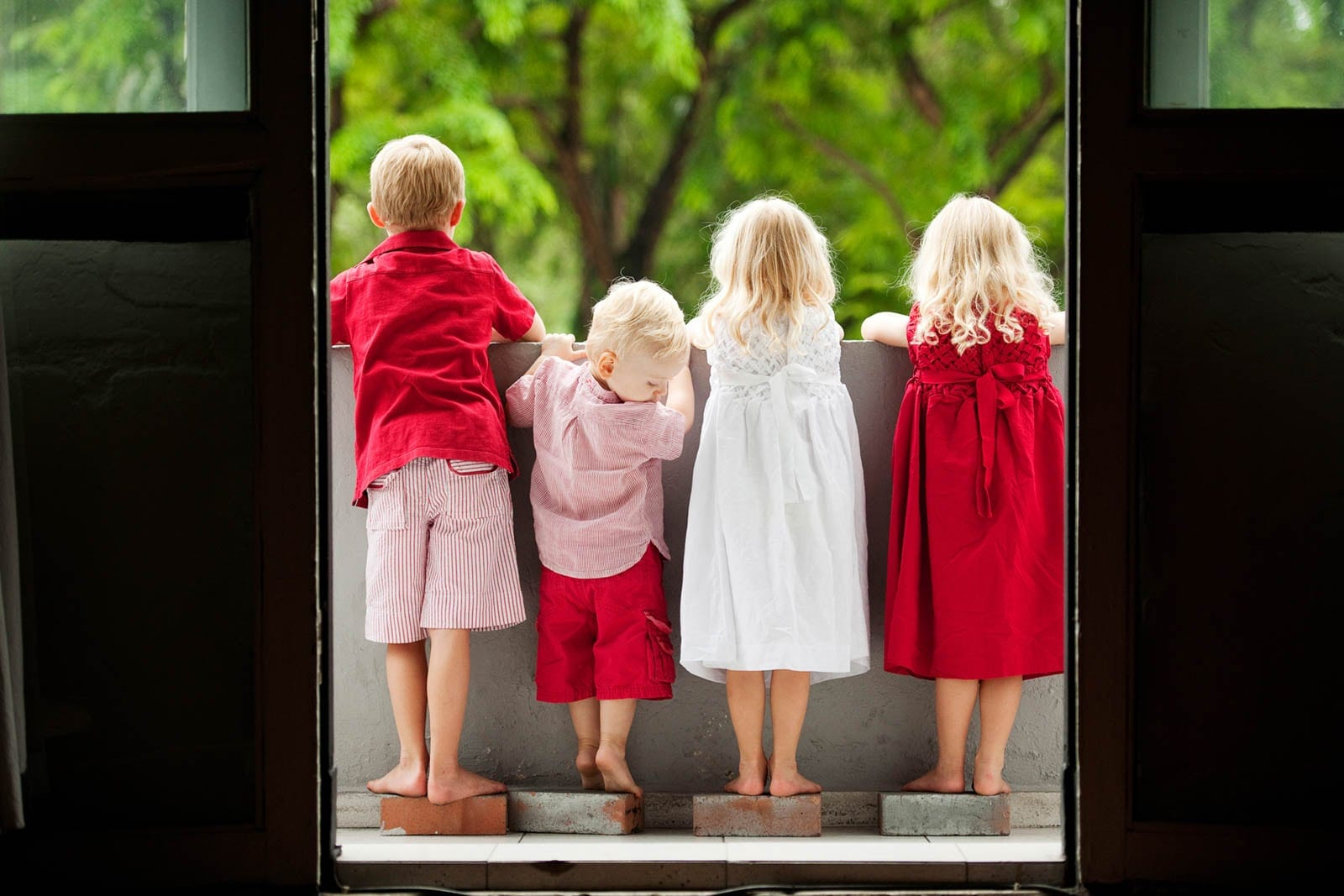 Kids Singapore Photoshoot back view of 4 children in red clothing looking out at a nature landscape