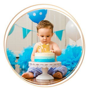 First Year Baby Cake Smash Photography baby touching birthday cake with blue decorations in background