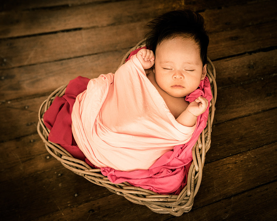 100 days old baby girl swaddled and sleeping peacefully in a heart-shape basket in White Room Studio