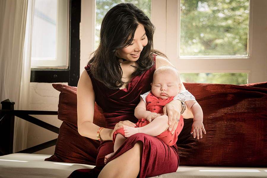 new mother with her 100 days old sleeping baby in peranakan shophouse white room studio