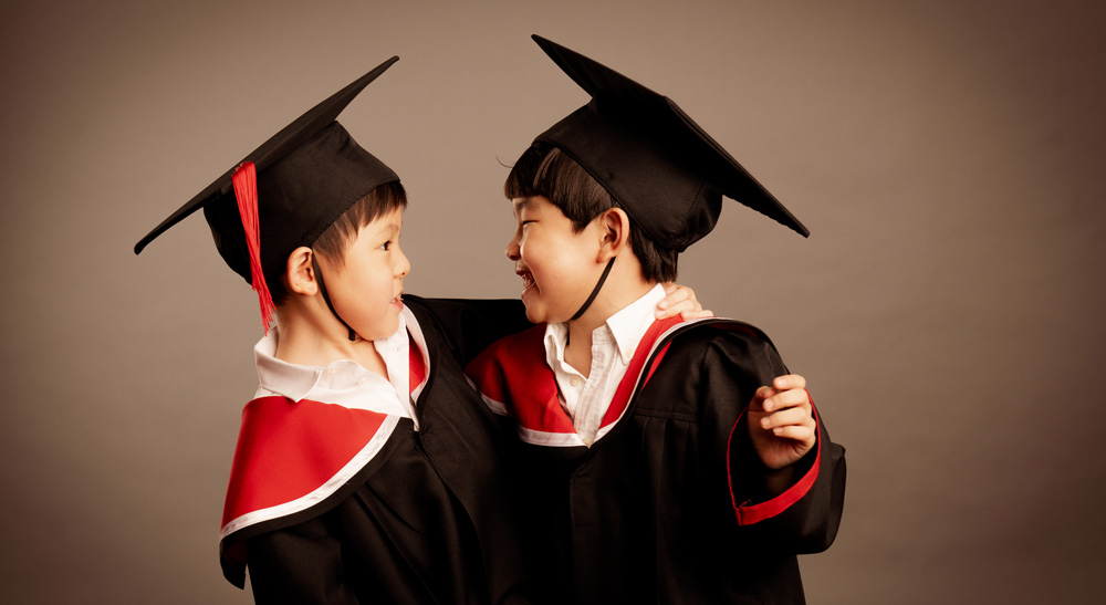 Best friends in kindergarten graduation gown during a photoshoot in photo studio White Room Studio