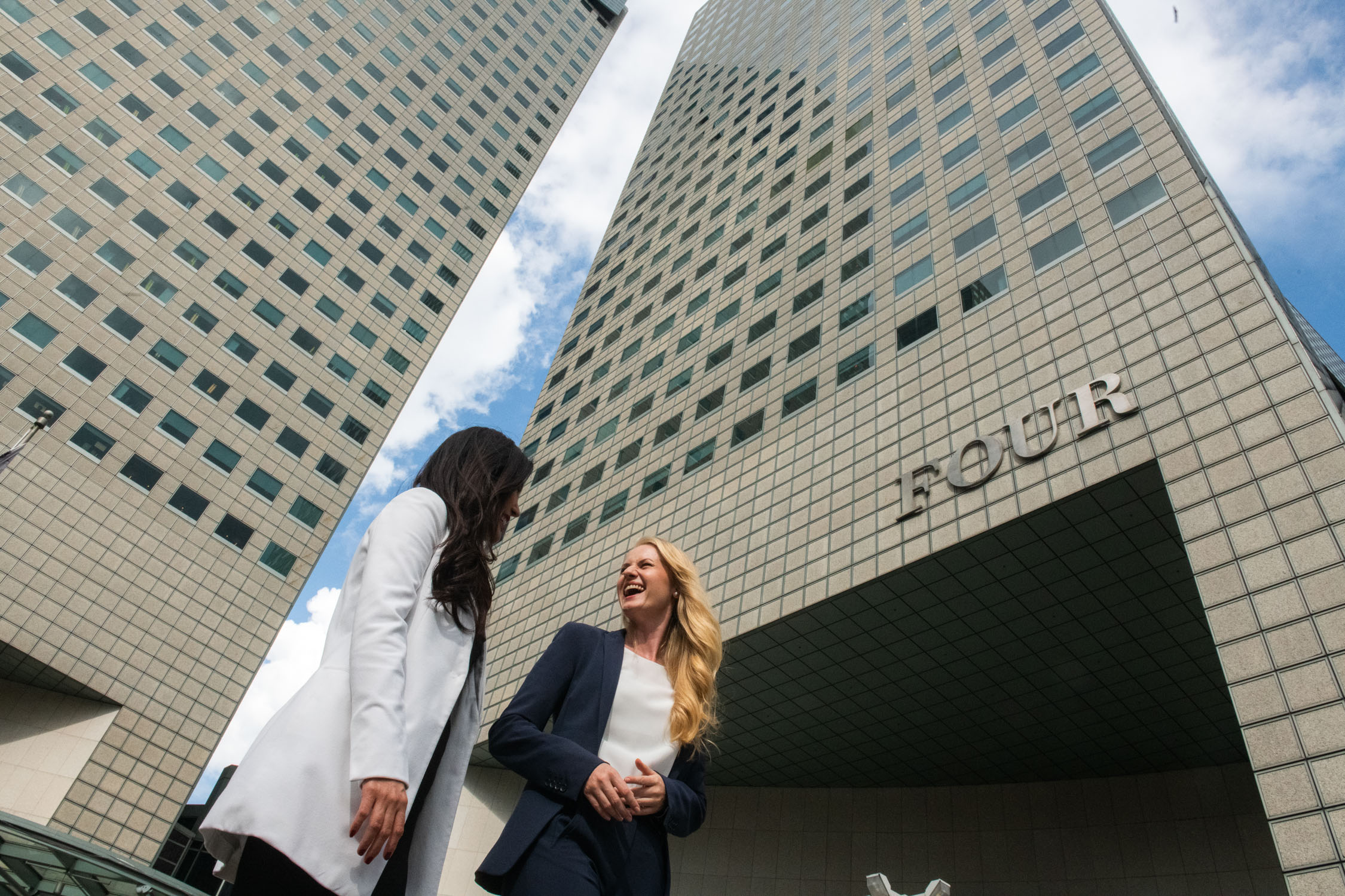 Two women in formal corporate attire walking and talking together outside an office building