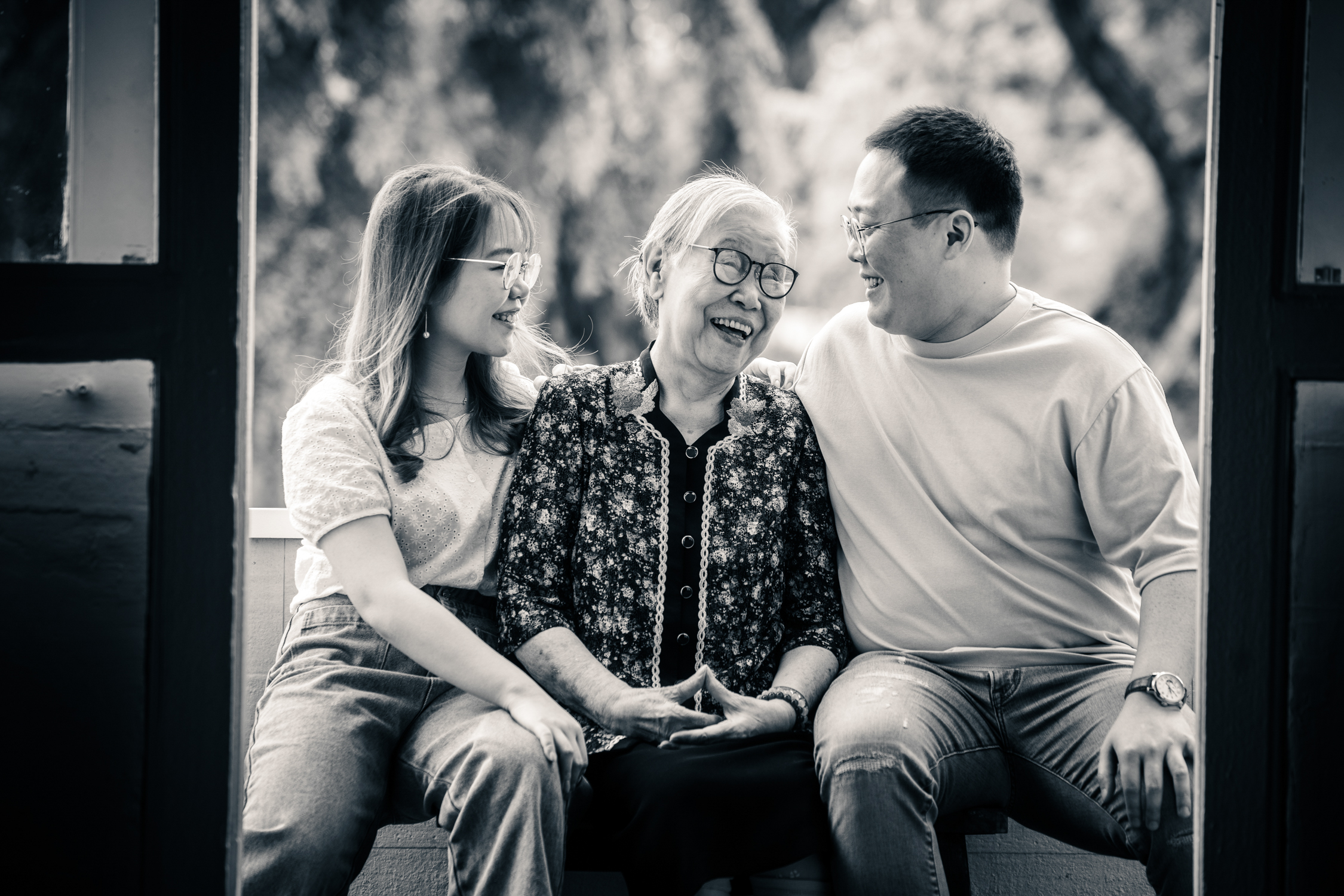 black and white photo of a grandmother smiling at her two grandchildren