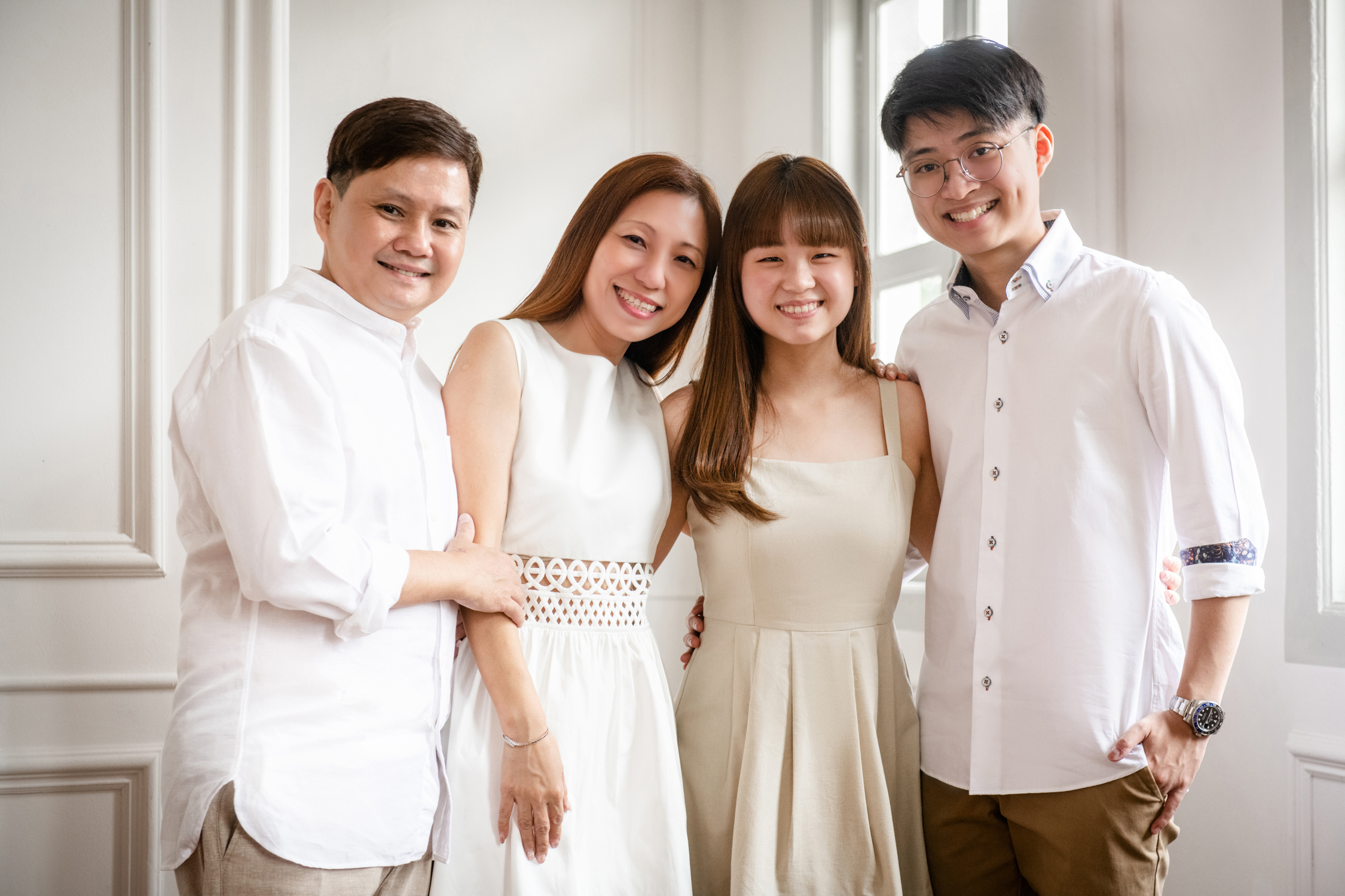 Family of four dressed in white, standing in front of a white wall