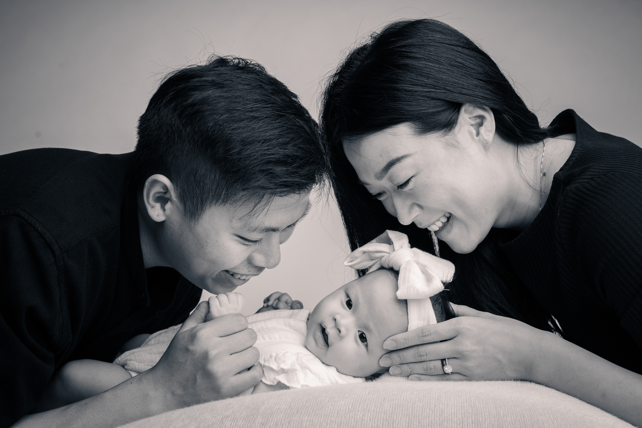 black and white photo of parents smiling at their child