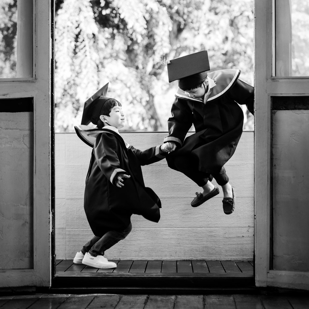 black and white photo of two children jumping