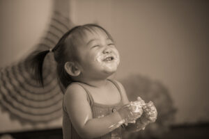 black and white photo of baby eating cake