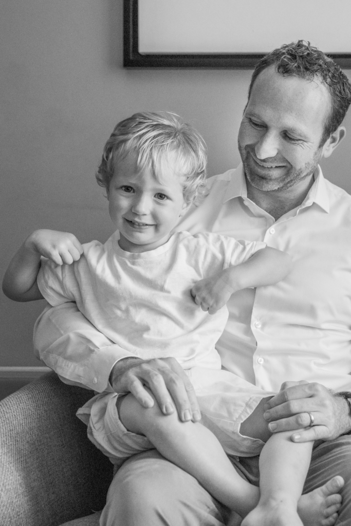 Black and white photo of a father carrying his young son on his lap