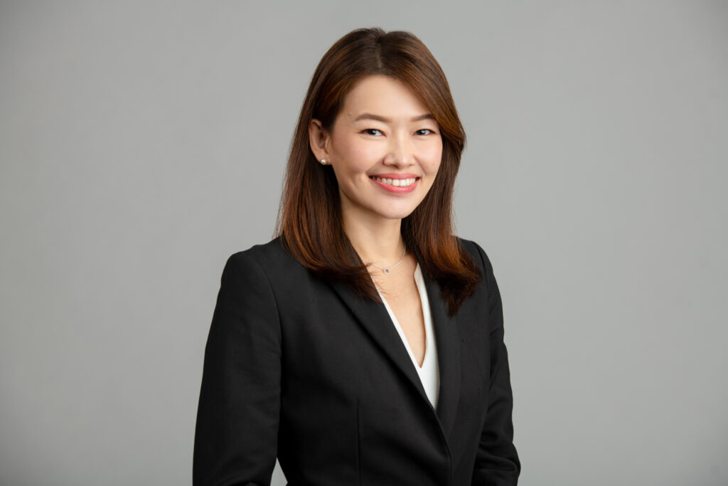 Asian woman in a formal corporate attire smiling for her headshot