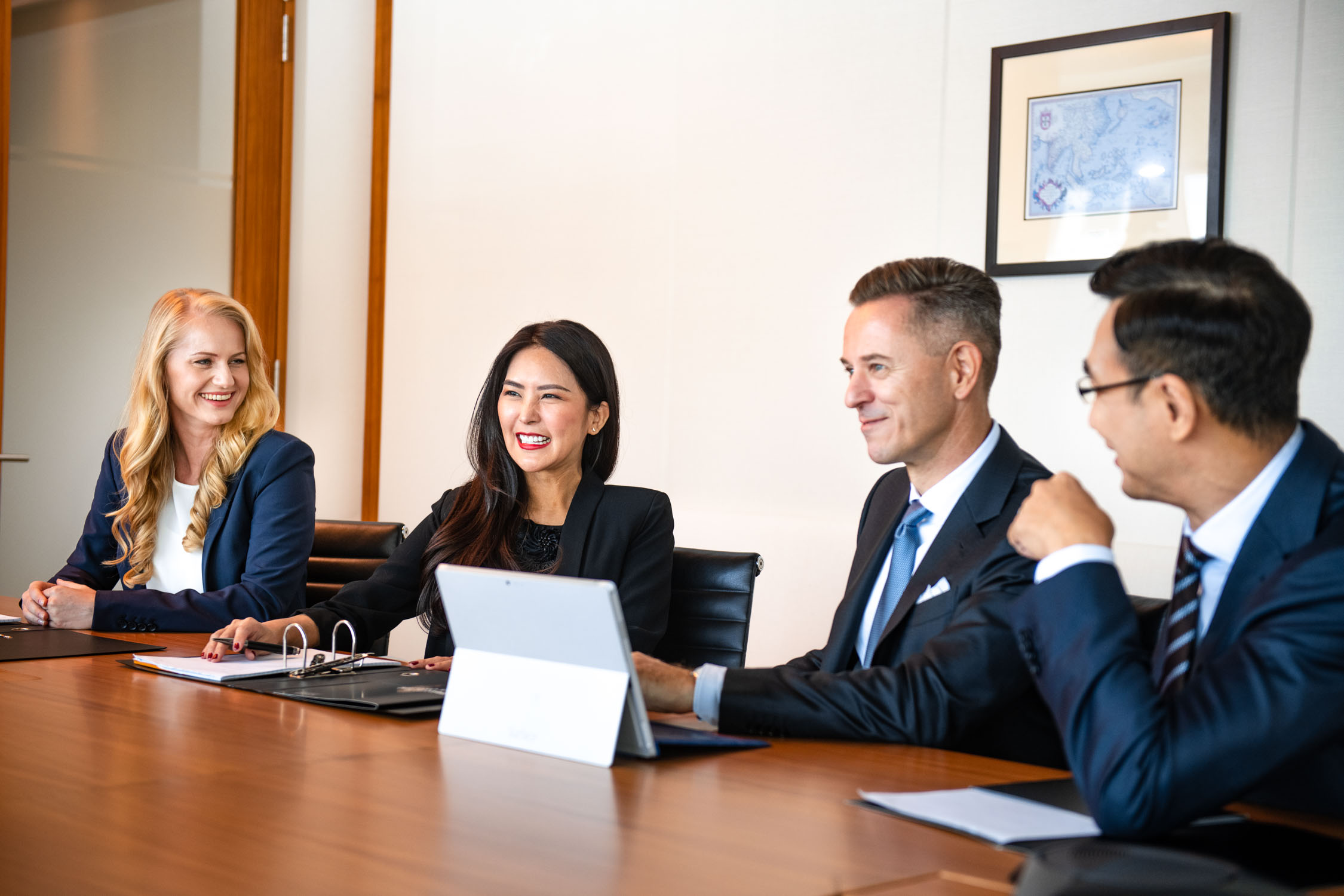 A group of corporate professionals (two women and two men) sitting down having a meeting in the office